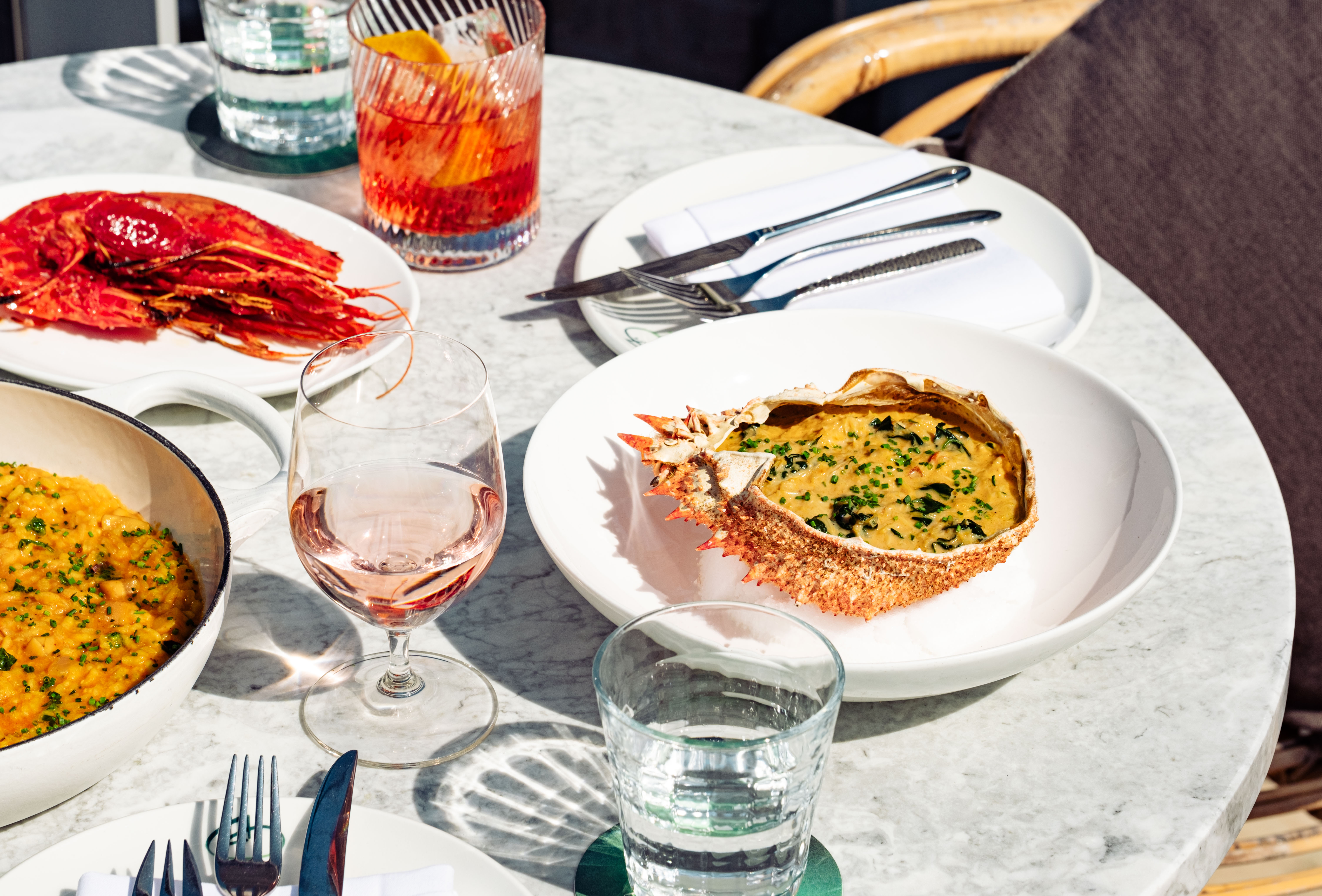 Table at Seabird Restaurant by The Hoxton with seafood dishes and drinks